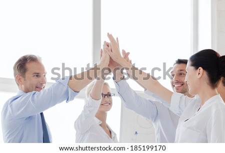 success and winning concept - happy business team giving high five in office - stock photo