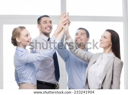success, business, office and winning concept - happy business team giving high five in office - stock photo