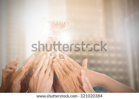 Success business with thier winner trophy holding by hands.  - stock photo