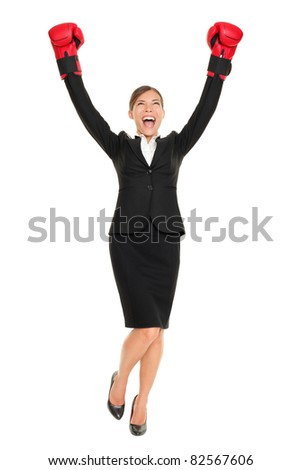 Success business woman cheering with arms in air wearing boxing gloves - business concept with businesswoman in full body celebrating happy. Young female professional isolated on white background. - stock photo