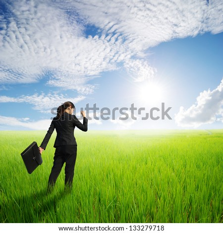 Success Business woman holding bag in green rice field and sun sky