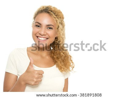 Success. Close up portrait of a young tanned girl with curvy dyed hair standing smiling and showing thumb up, isolated on white background - stock photo