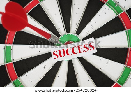 Success Concept and a dart in center of target - stock photo
