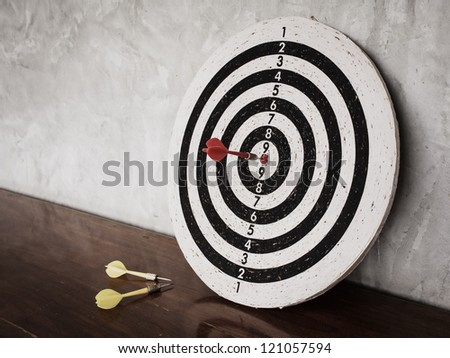 Success concept, darts hit target on dartboard - stock photo