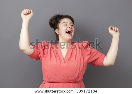 success concept - ecstatic young fat girl dancing wearing a vintage dress expressing her achievement and energy