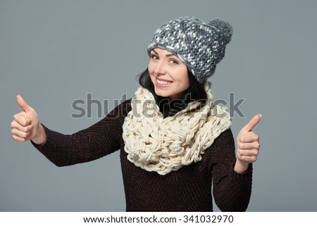 Success concept. Happy beautiful woman wearing warm winter clothing giving double thumbs up, over grey background - stock photo