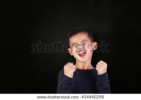 Success concept, portrait of happy young Asian boy showing enthusiastic winning gesture shout with joy of victory over blackboard - stock photo