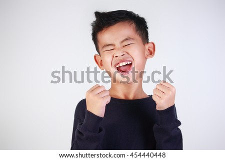 Success concept, portrait of happy young Asian boy showing enthusiastic winning gesture shout with joy of victory - stock photo