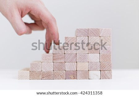 Success concept with businessman hand climbing wooden block stairs on white background - stock photo