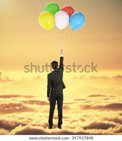 Success concept with businessman holding onto colorful balloons in yellow skies