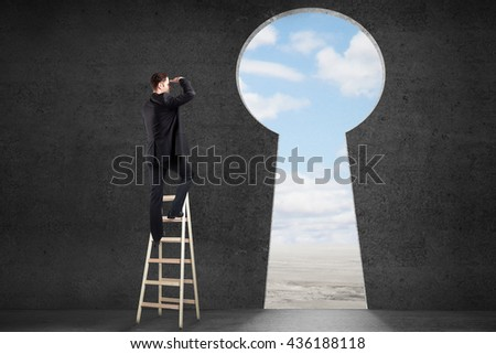 Success concept with businessman on ladder looking through keyhole shaped door with clear sky view in concrete room - stock photo