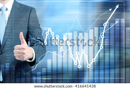 Success concept with businessman showing thumbs up next to business chart - stock photo