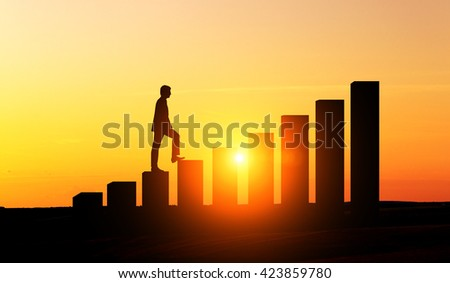 Success concept with businessman silhouette climbing chart bars at sunset - stock photo