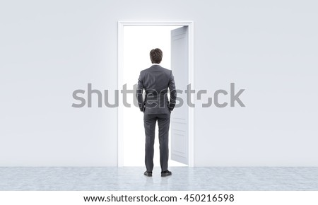 Success concept with businessman standing in concrete interior in front of open door with bright light
