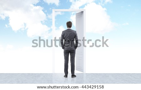 Success concept with businessman standing in front of open door on sky background