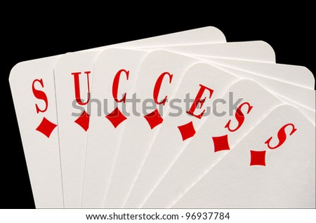 Success concept with playing cards isolated over black - stock photo