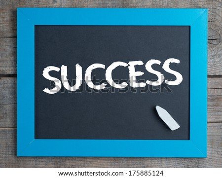 Success. Creative composition with the message Success on blackboard on wooden table - stock photo