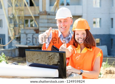 success female and male construction workers   with a laptop and drawings - stock photo