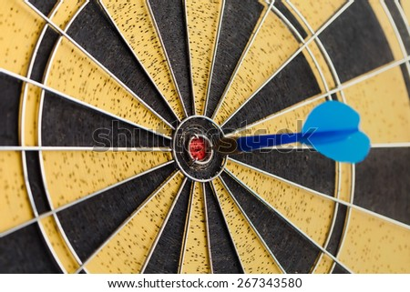 Success hitting target aim goal achievement. Blue Dart in bull's eye. Retro darts aim. (soft focus, toned photo) - stock photo