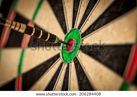 Success hitting target aim goal achievement concept background - dart in bull's eye close up - stock photo