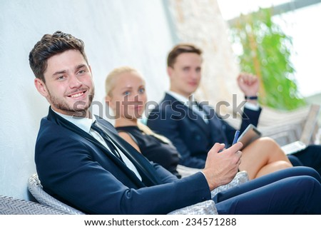 Success in business. Smiling businessman sitting in board room and holding a mobile tablet in his hands while his colleagues sitting behind. Businesspeople sitting in line and dressed in formal wear. - stock photo