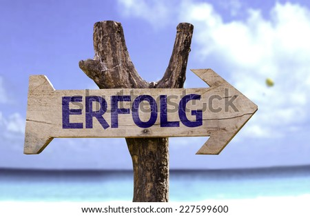 Success (In German) wooden sign with a beach on background - stock photo