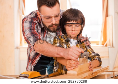 Success is a learnable skill. Concentrated young male carpenter teaching his son to work with wood in his workshop - stock photo
