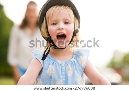 Success is... finally learning how to ride your bike. A blonde girl cheers happily, so proud that she has learned how to ride her bike. In the background, the mother stands watching her daughter. - stock photo