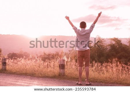 success man hold up hands to sun light, color process - stock photo