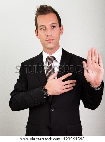 Success Man With Arm On Chest Taking Oath - stock photo