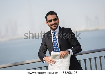 Success manager in formal suit staying in waterfront. Arabian Businessman holding newspaper.