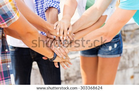 success, people, teamwork and gesture concept - cclose up of friends hands on top of each other outdoors - stock photo