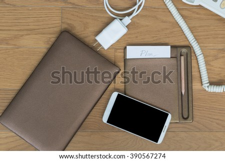 Success plan notepad, pencil near smartphone, mobile charger on office wooden table.