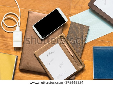 Success plan notepad, pencil near smartphone, mobile charger on office wooden table.business concept.