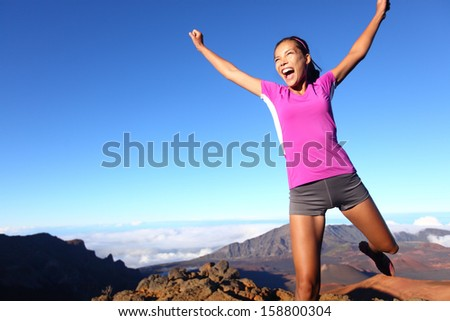 Success winner fitness runner woman jumping happy, excited and energetic with happy cheering face expression celebrating. Sporty running girl cheering after training outdoor in volcano landscape. - stock photo