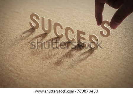 SUCCESS wood word on compressed or corkboard with human's finger at S letter.