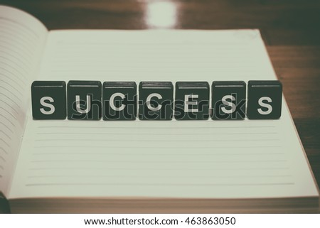 Success word from black plastic blocks on notebook with vintage filter background