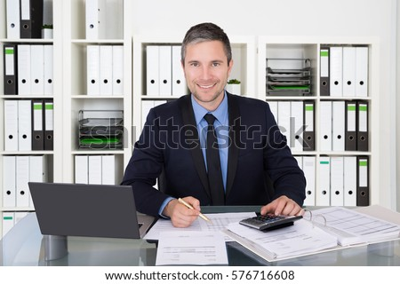 Successful Accountant Calculating Tax Invoice At Office Desk Using  Calculator And Laptop