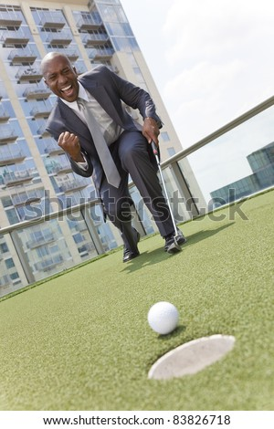Successful African American businessman or man in a suit playing golf on a corporate putting green on roof of a skyscraper office building