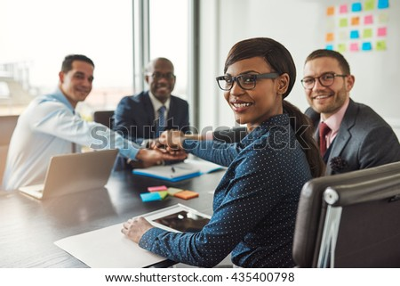 Successful African American team leader turning to smile at the camera as her multiracial team of executives links hands across the table - stock photo