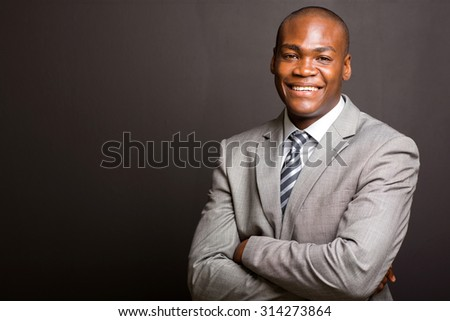 successful african business man with arms folded on black background - stock photo