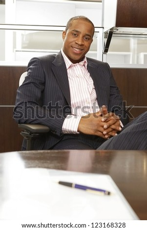 Successful African businessman relaxing in a chair in front of his desk at the office - stock photo