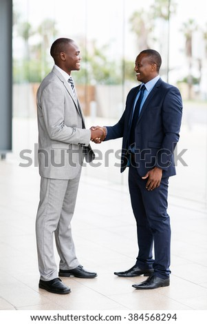 successful african businessmen handshaking in conference hall - stock photo