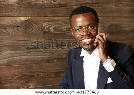 Successful African entrepreneur in formal two-piece suit looking and smiling at the camera with happy expression while making phone calls sitting at the cafe isolated against wooden wall background
