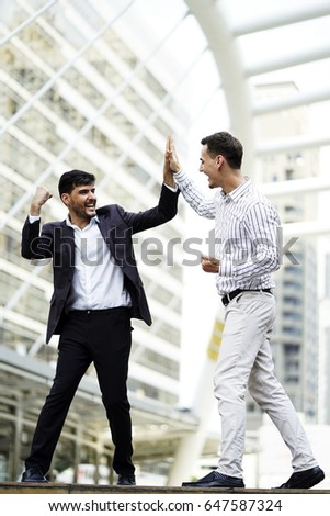 Successful and happiness two business man suit high five together outdoor