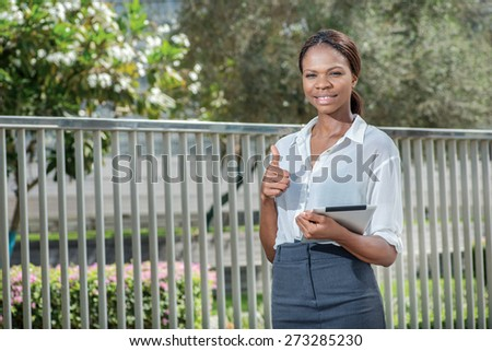 Successful and happy business. African businesswoman businessman holding a tablet in her hand while standing on the street and looking into the camera showing a thumbs up - stock photo