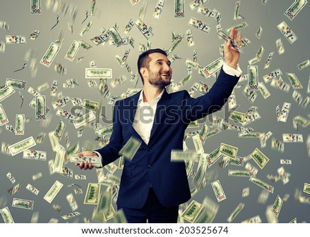 successful and smiley businessman catching money under dollar's rain - stock photo