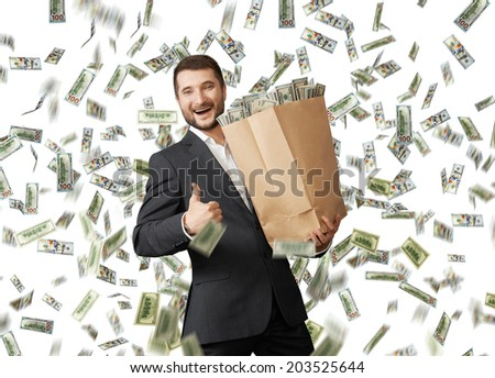 successful and smiley businessman holding paper bag under dollar's rain and showing thumbs up - stock photo
