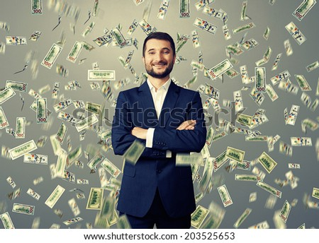 successful and smiley businessman under dollar's rain over grey background