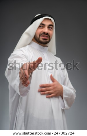 Successful arab businessman. Closeup low angle image with selective focus of Arab business man stretching out his hand while standing against grey background - stock photo